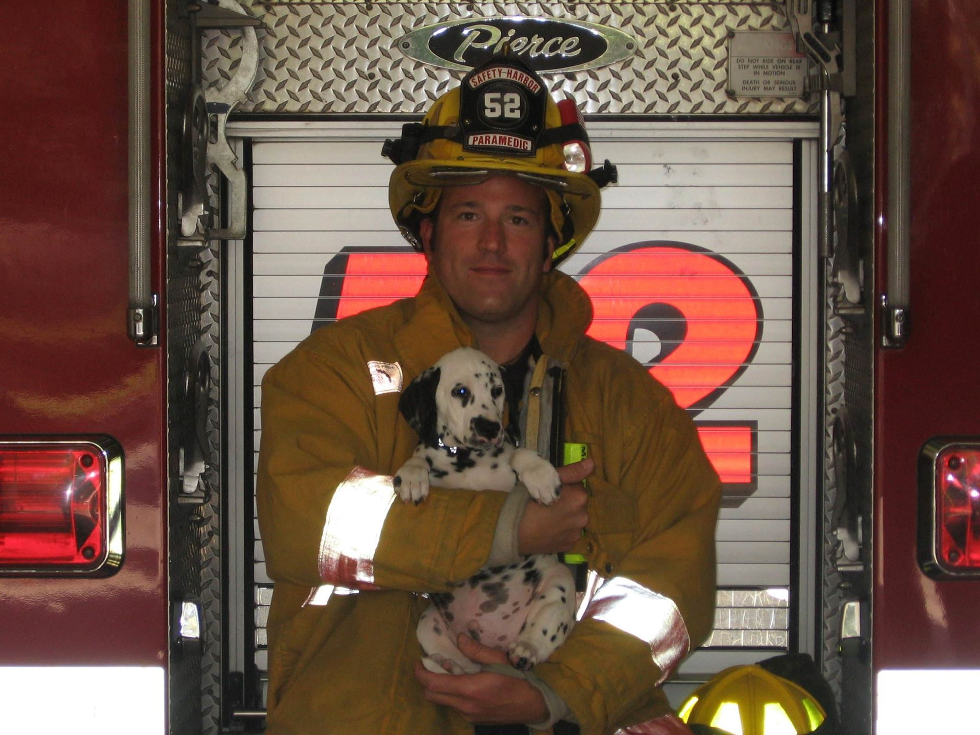 A firefighter holds a dalmation puppy