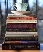 stack of books with a tea cup resting on top.