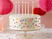 Polka dot birthday cake with 6 lit candles.