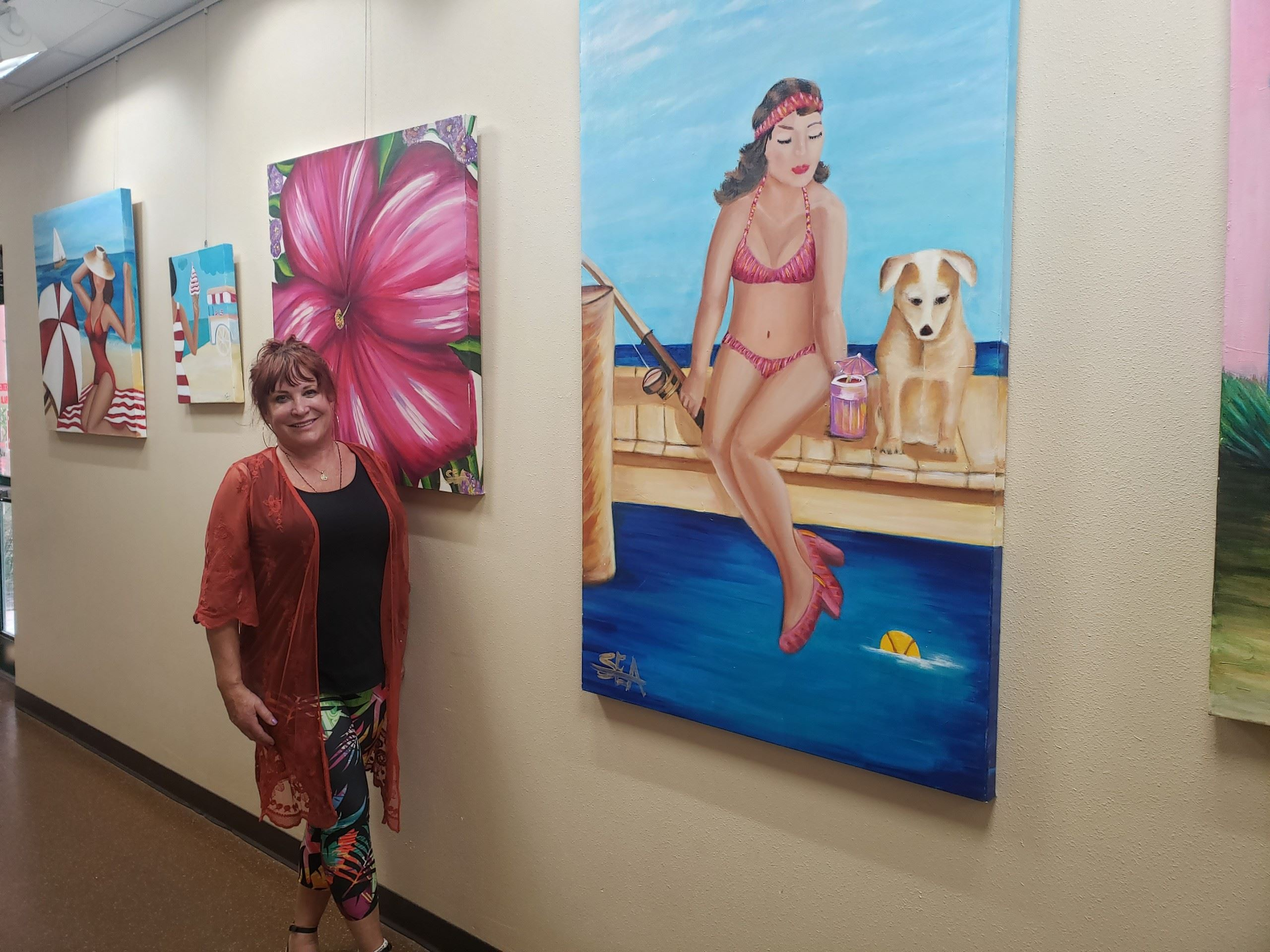 Artist Shelly E. Augsbury next to four of her paintings.