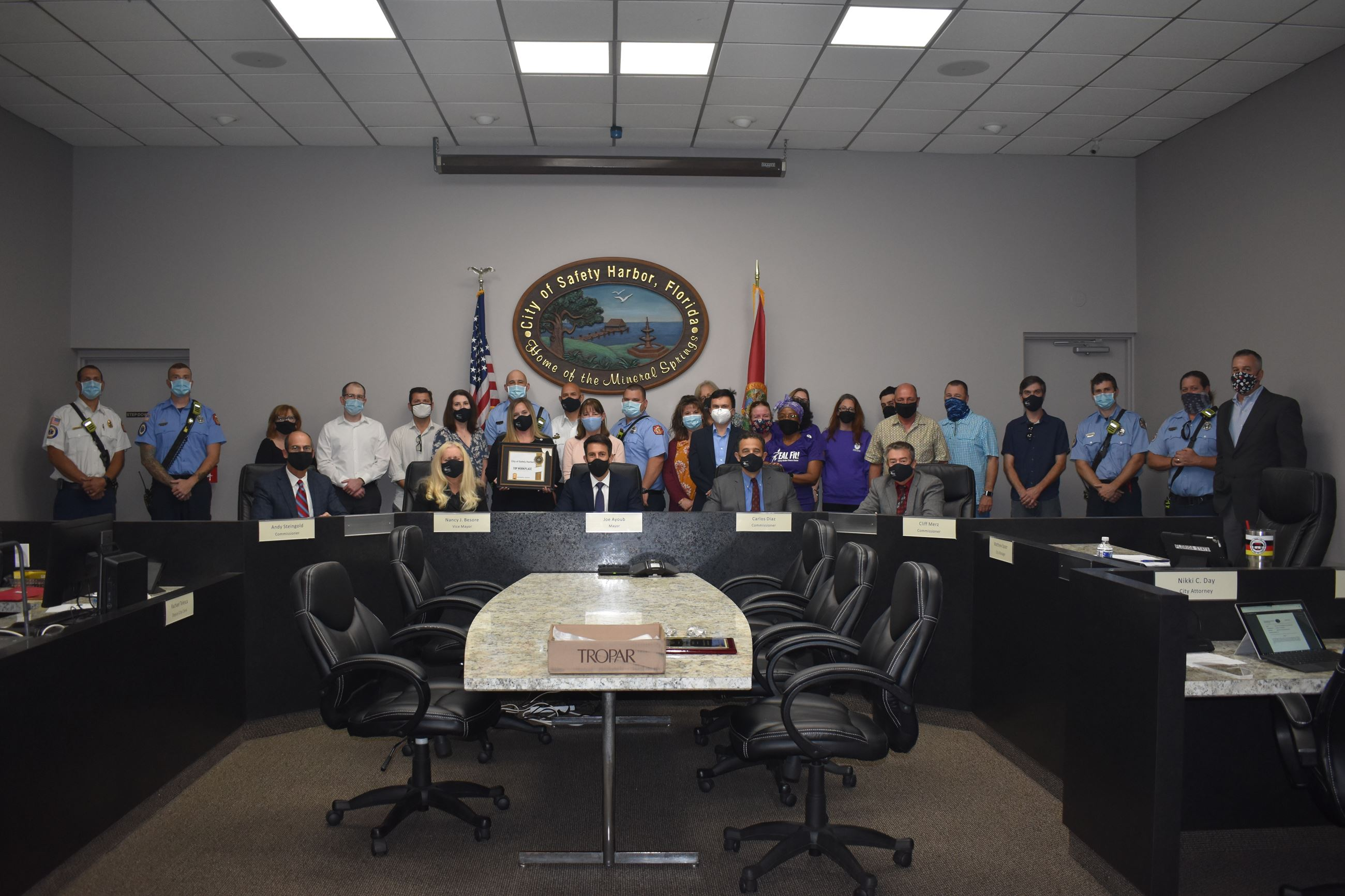 Safety Harbor employees from various departments accept Top Workplace plaque from City Commission